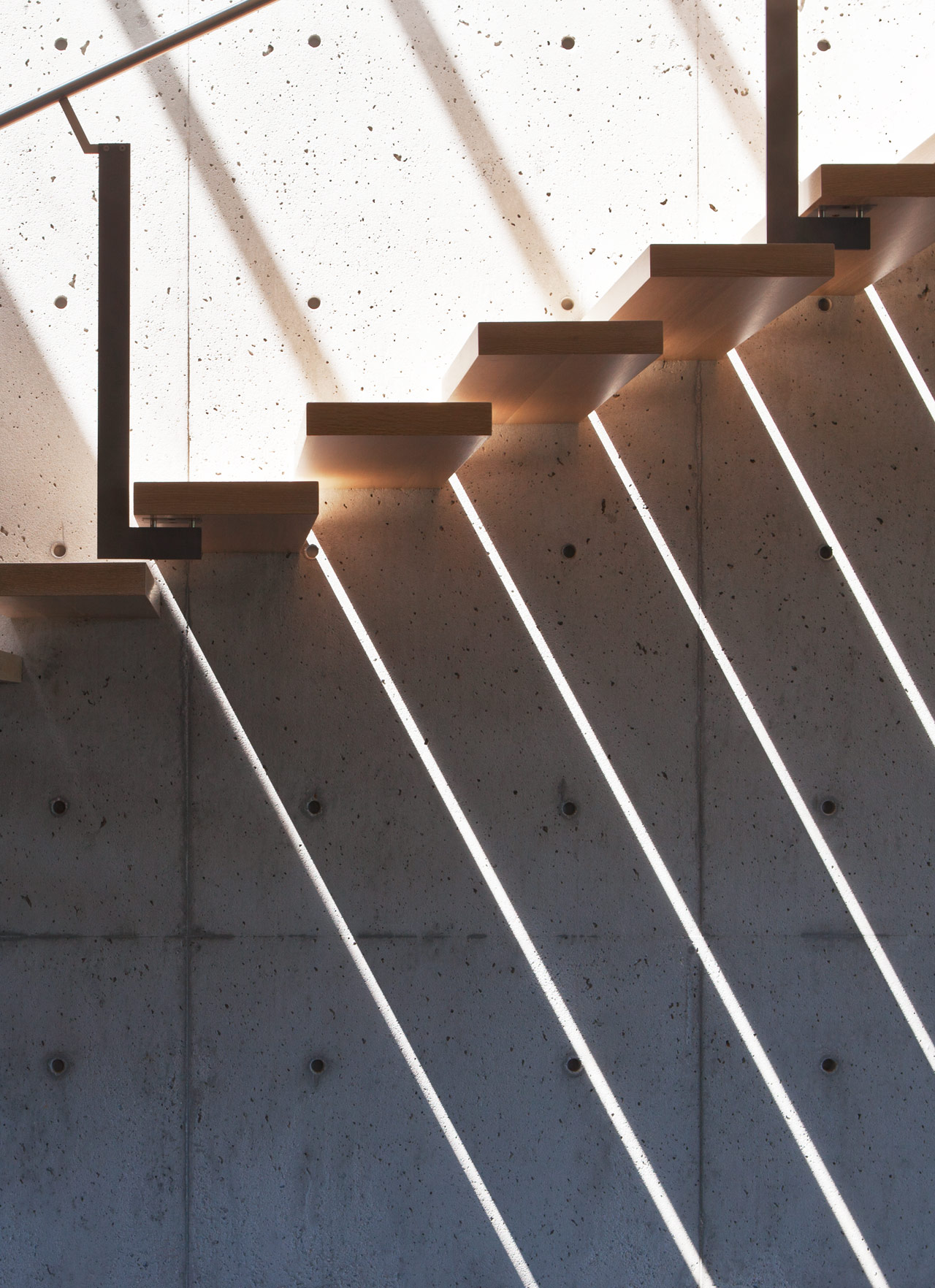 Light shining through slits in floating wood staircase against concrete wall.
