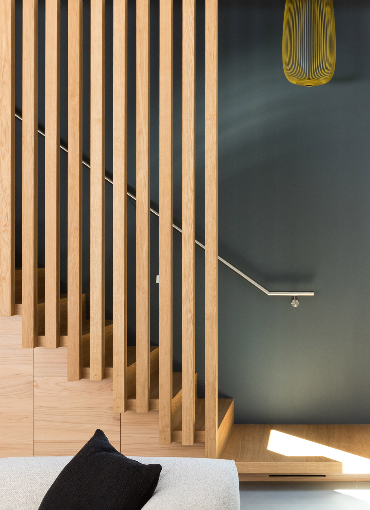Wooden staircase set against deep green wall.