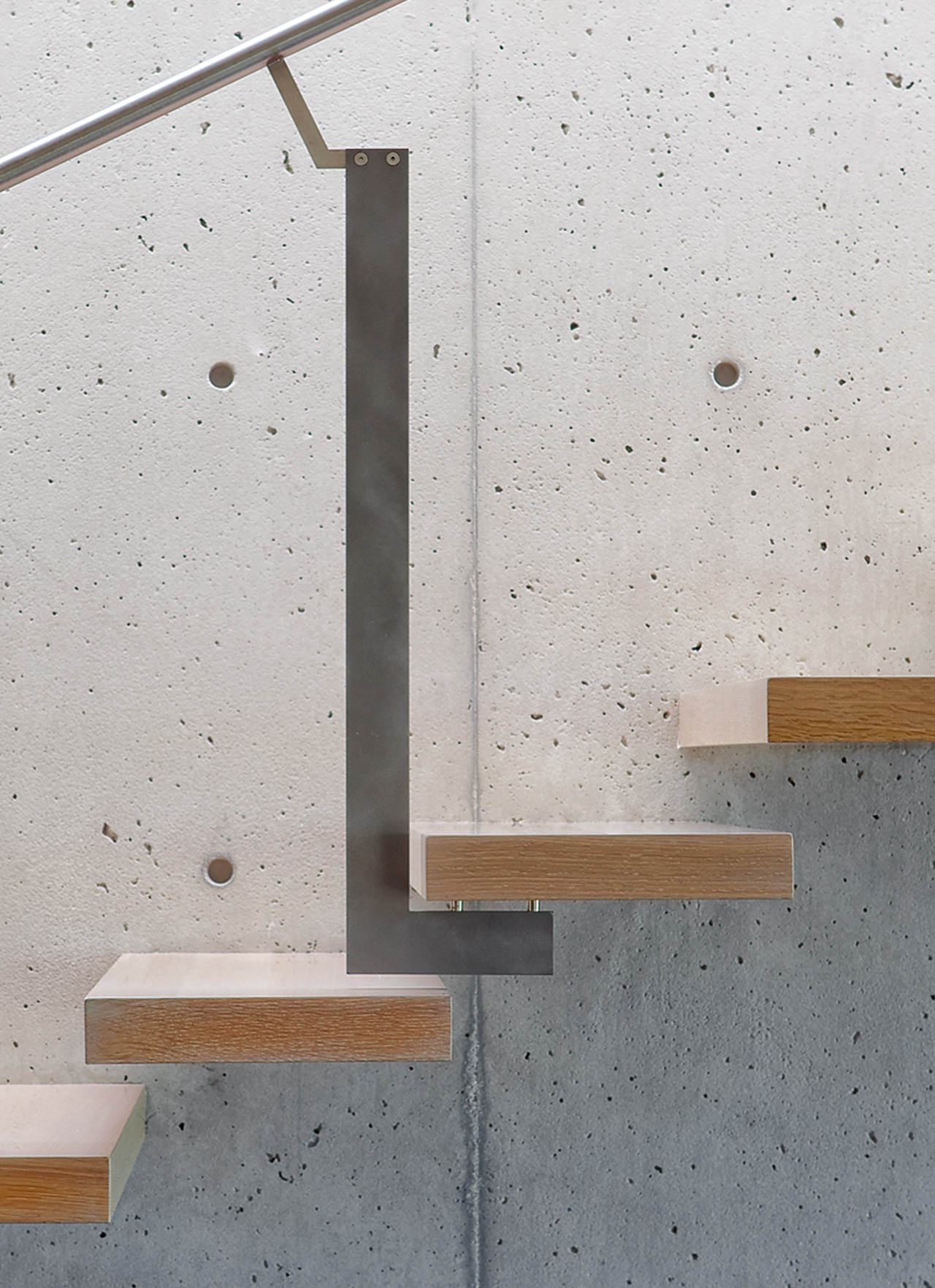 Floating wood stairs against concrete wall.