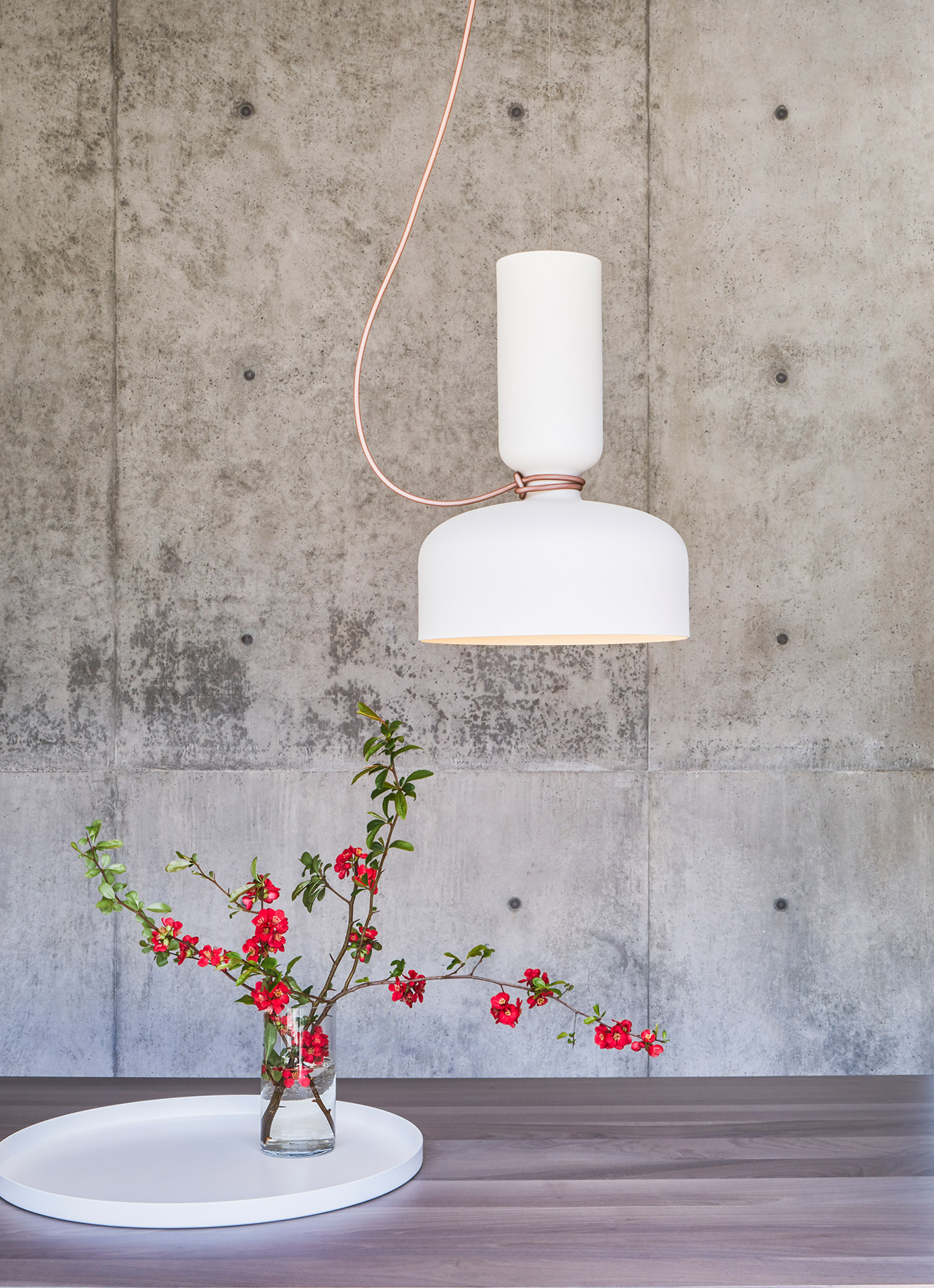 Modern white light fixture above table against a concrete wall.